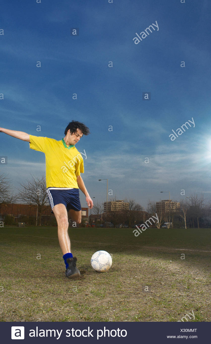 footballer kicking ball - Stock Image