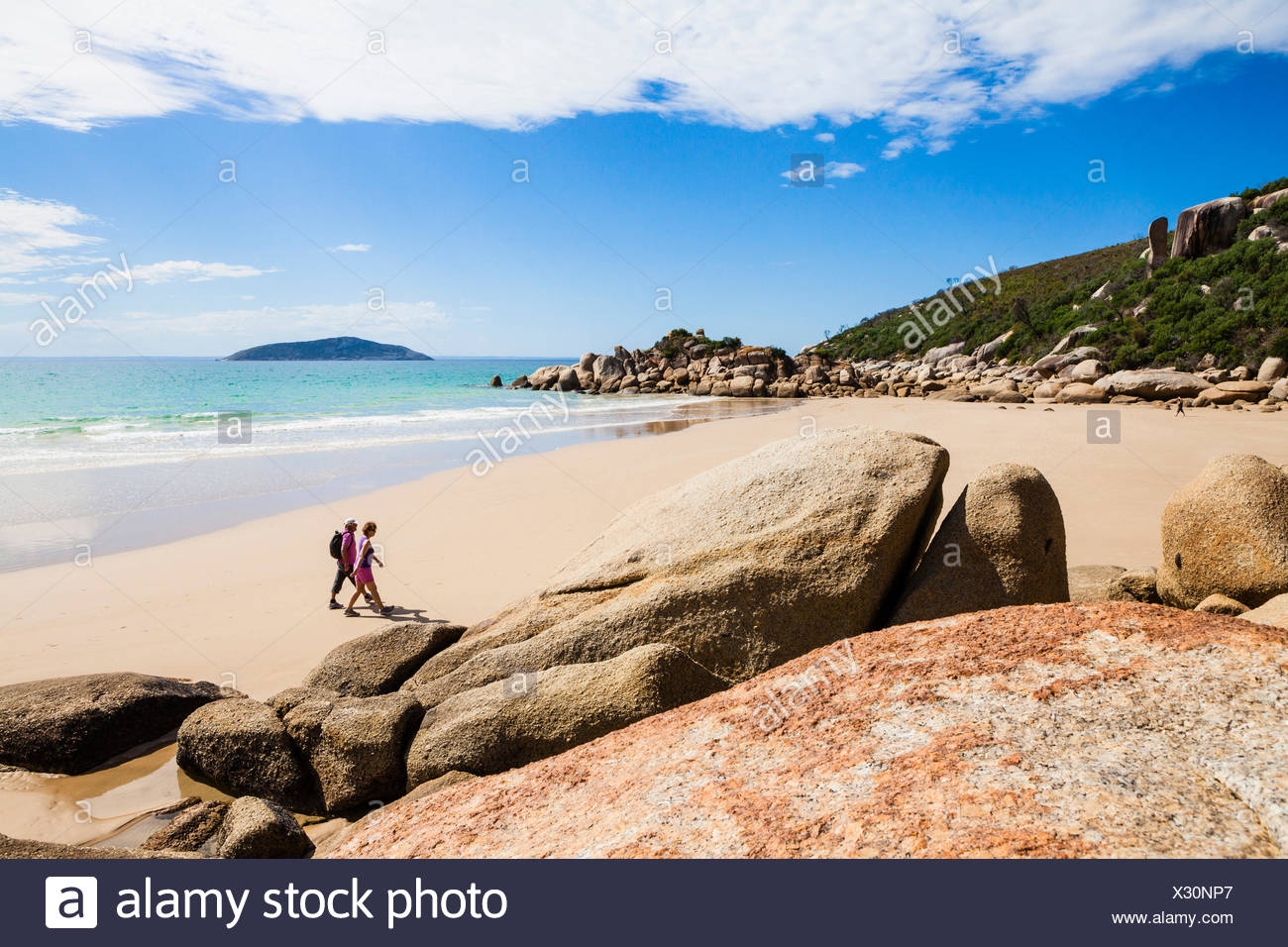 Two persons walking at beach of Fairy Cove, Wilsons Promontory, Victoria, Australia - Stock Image
