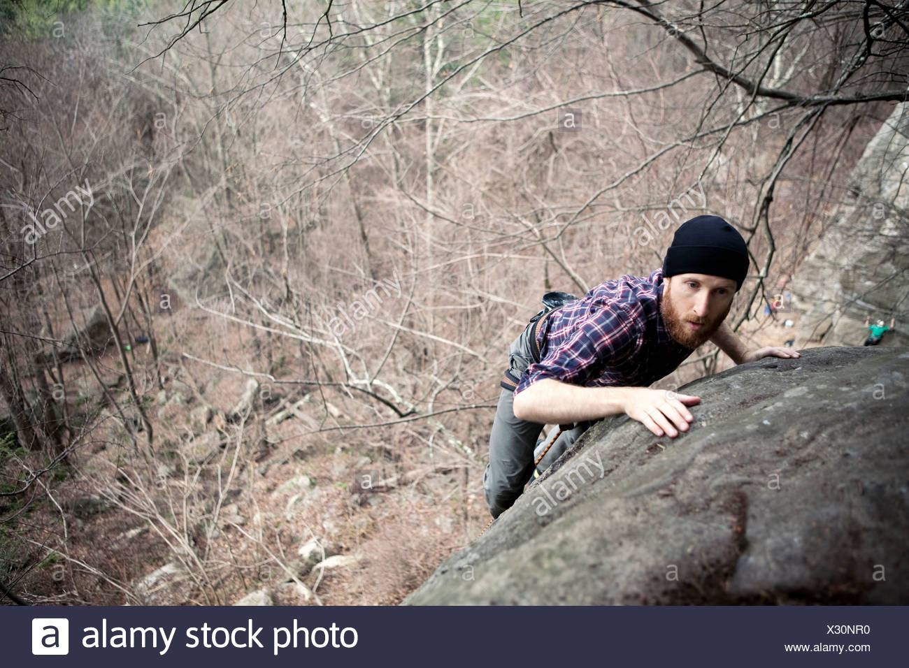 A male rock climber tops on while climbing on a cold day in the northeast. - Stock Image