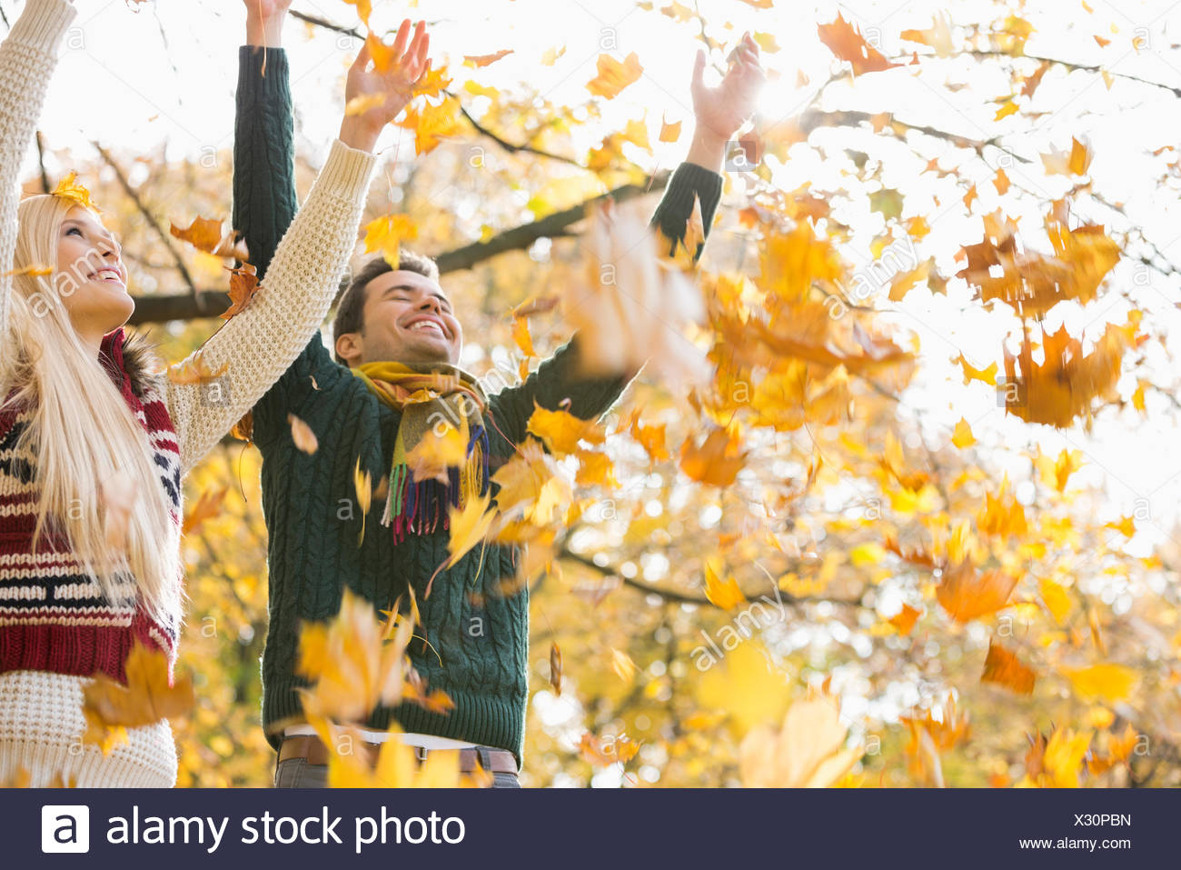 Young couple enjoying falling autumn leaves in park - Stock Image