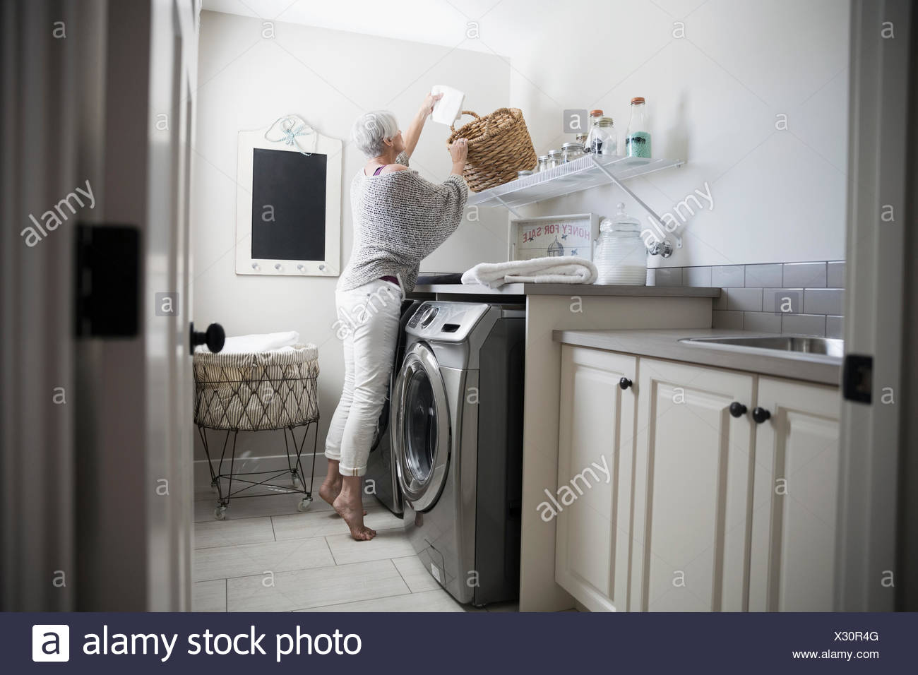 Woman reaching for basket in laundry room - Stock Image
