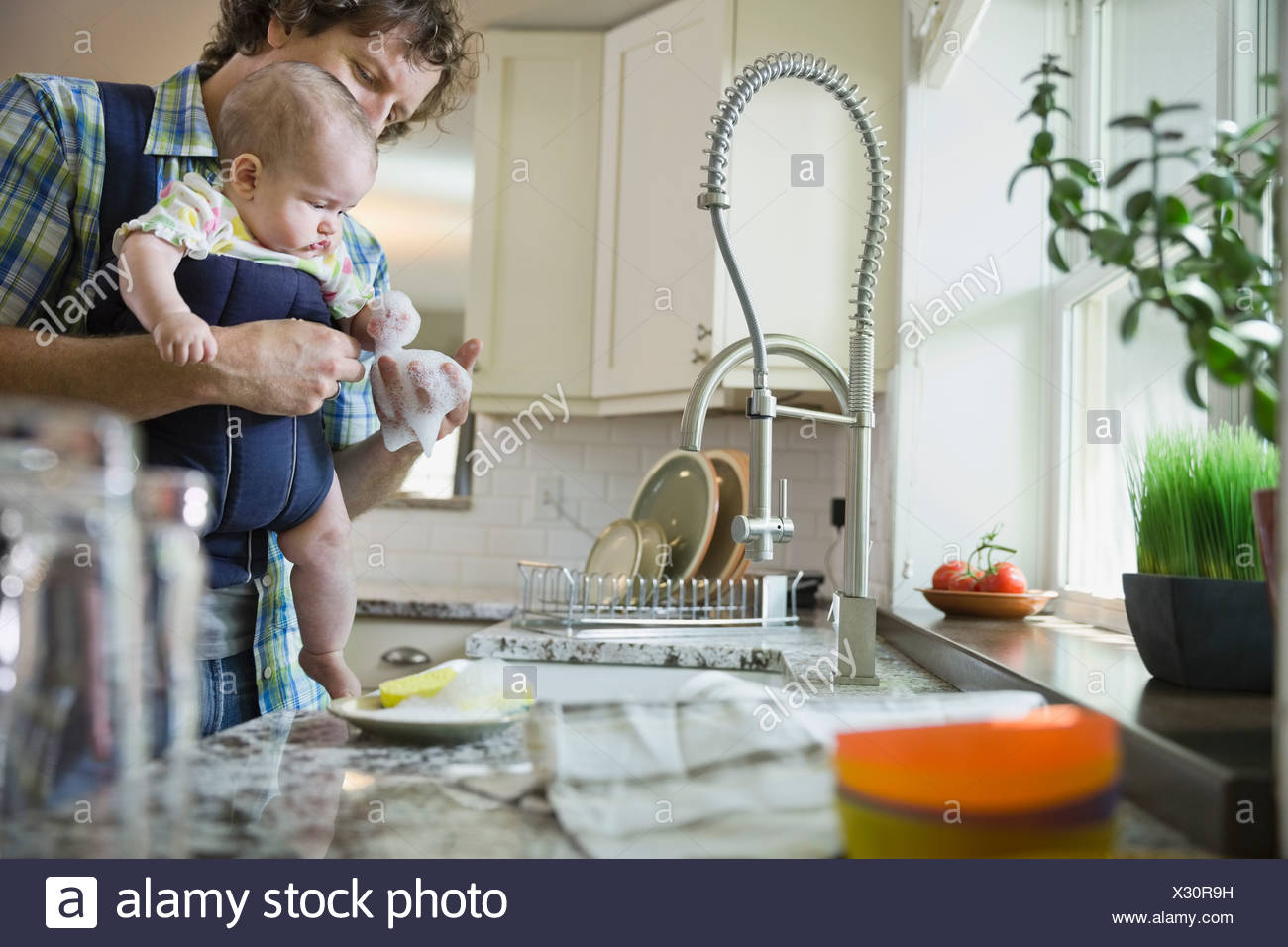 Father holding baby girl while washing dishes - Stock Image