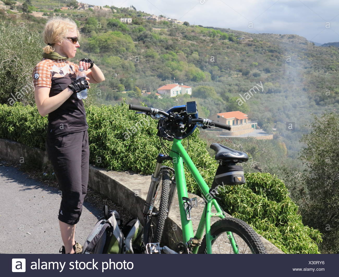 Woman taking a refreshment from a water bottle during a mountain bike ride on the Italian Riviera, Liguria, Italy, Europe - Stock Image