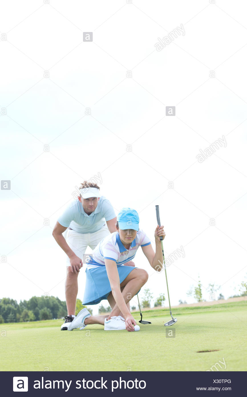 Man looking at woman aiming ball on golf course against sky - Stock Image