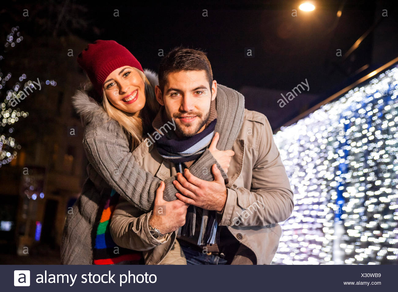 Portrait of happy young couple at Christmas Market - Stock Image