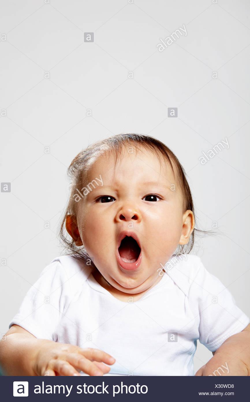 Portrait of baby girl yawning - Stock Image