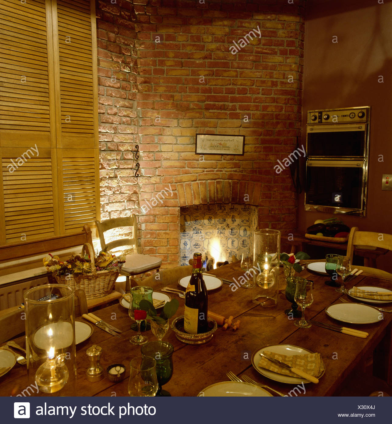 Dining Table With Place Settings Beside Fireplace In Brick Wall Stock Photo Alamy