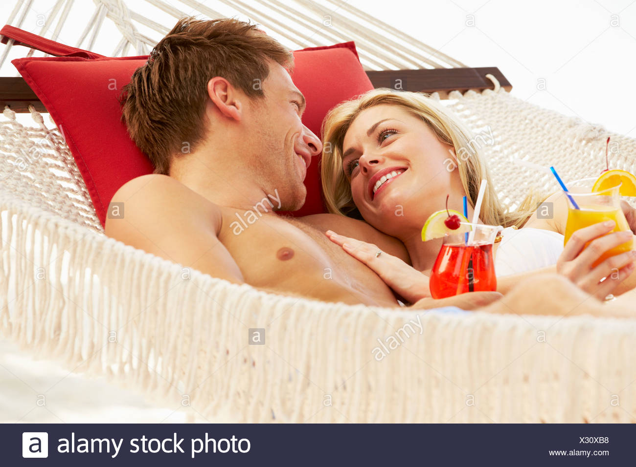 Romantic Couple Relaxing In Beach Hammock - Stock Image