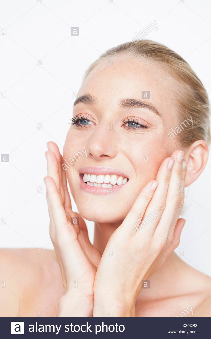 Bare shouldered woman with hands to face looking away smiling - Stock Image