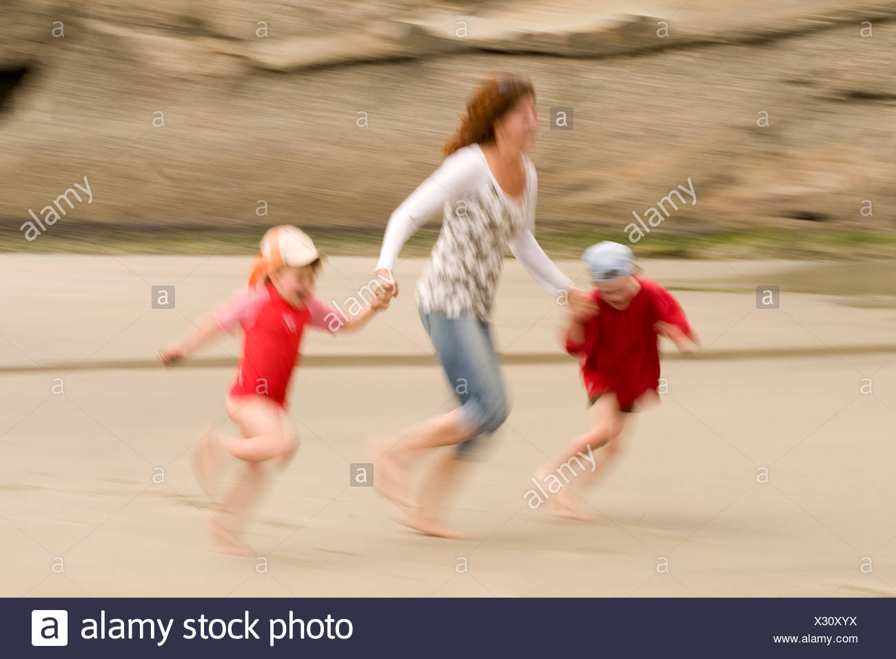 New Zealand, Cape Farewell, Woman with children (4-5) (6-7) on the beach, having fun Stock Photo