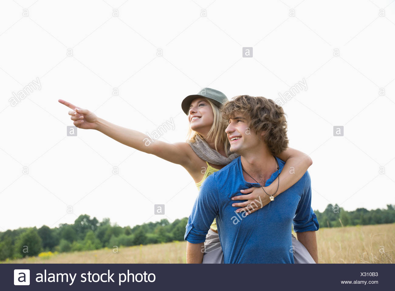 Happy woman showing something while enjoying piggyback ride on man in field - Stock Image