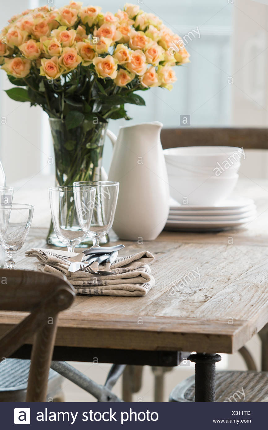 Rose bouquet and dinnerware wooden dining table - Stock Image