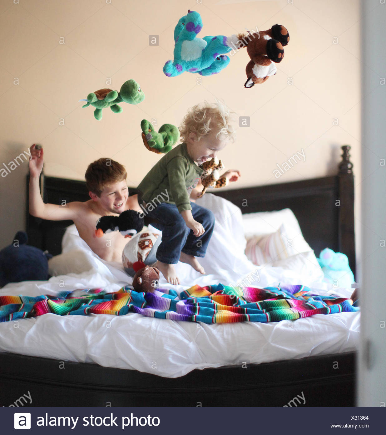 Boy jumping on brothers bed and throwing soft toys in the air - Stock Image