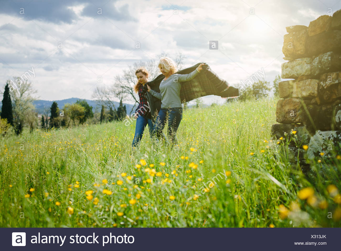 Mother and teenage daughter strolling with blanket - Stock Image