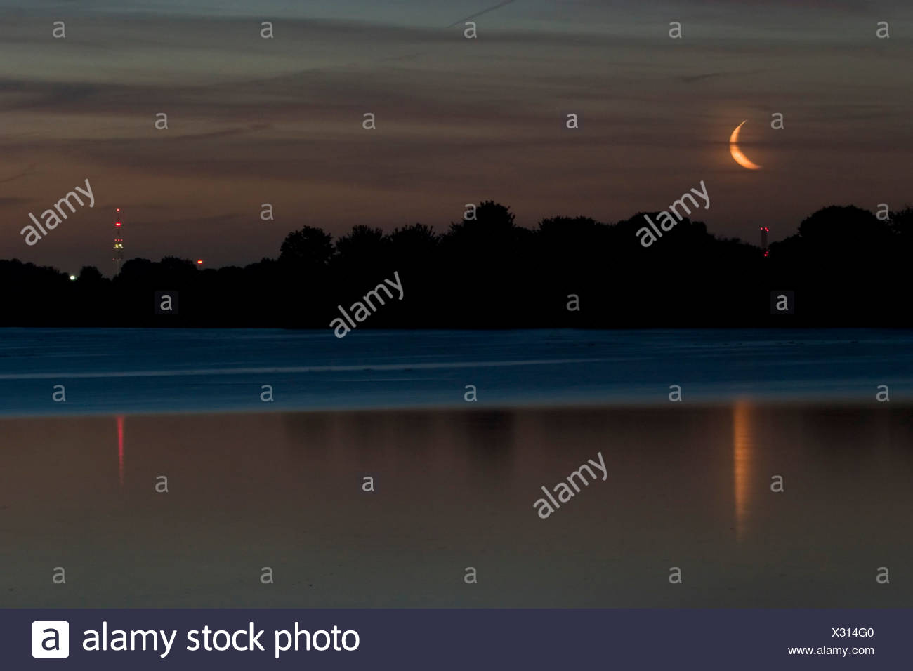 Moonshine over a lake with the lit olympic tower. Munich, Bavaria, Germany - Stock Image