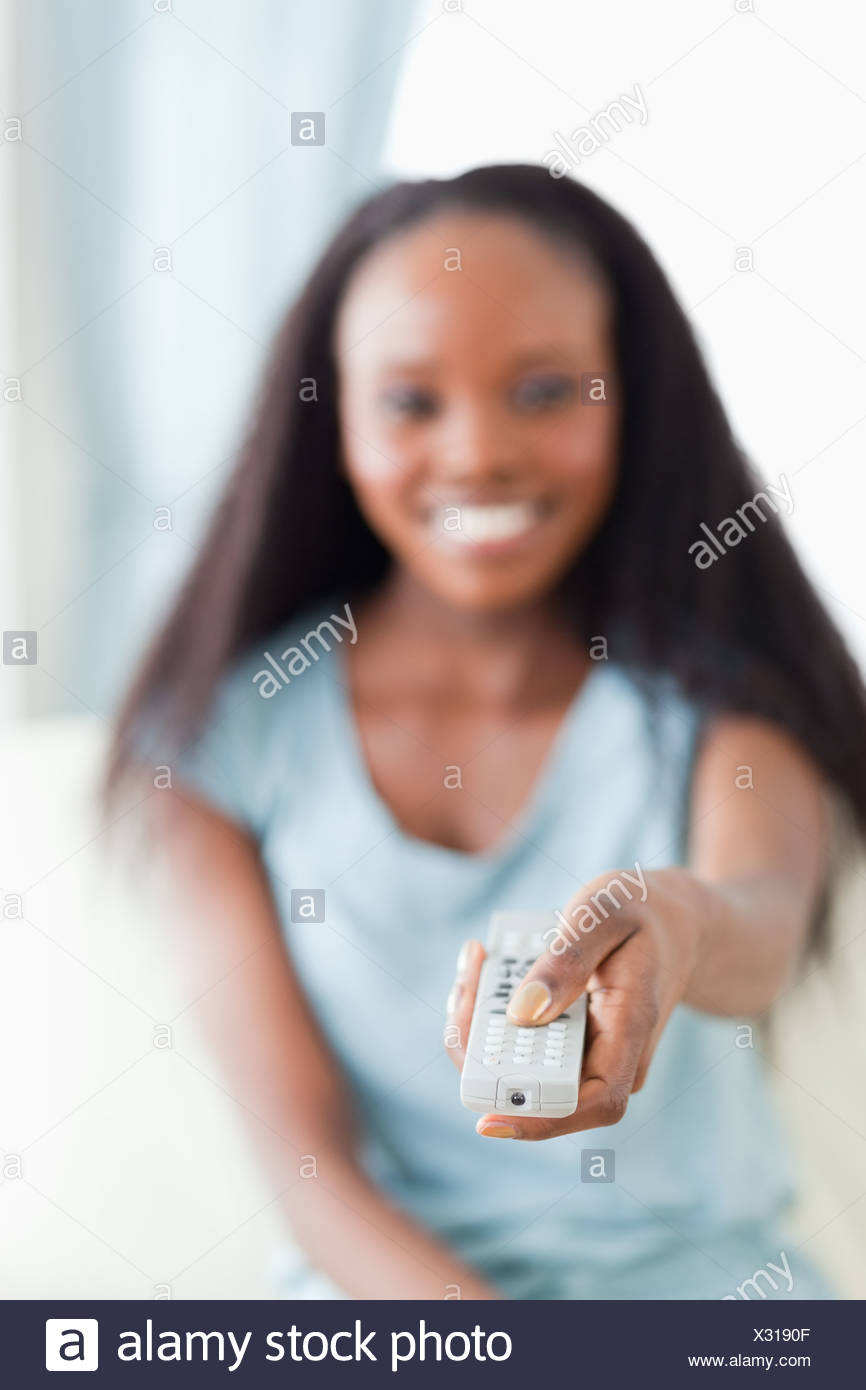 Close up of remote being used by woman - Stock Image
