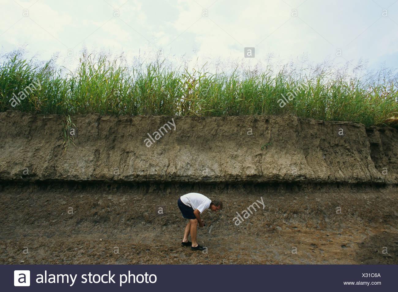 Man beside a mud bank hunting for arrowheads at Big Eddy MO