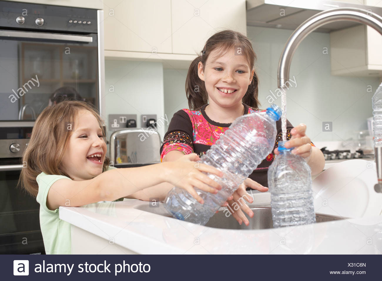 Girls filling up water bottle in kitchen Stock Photo