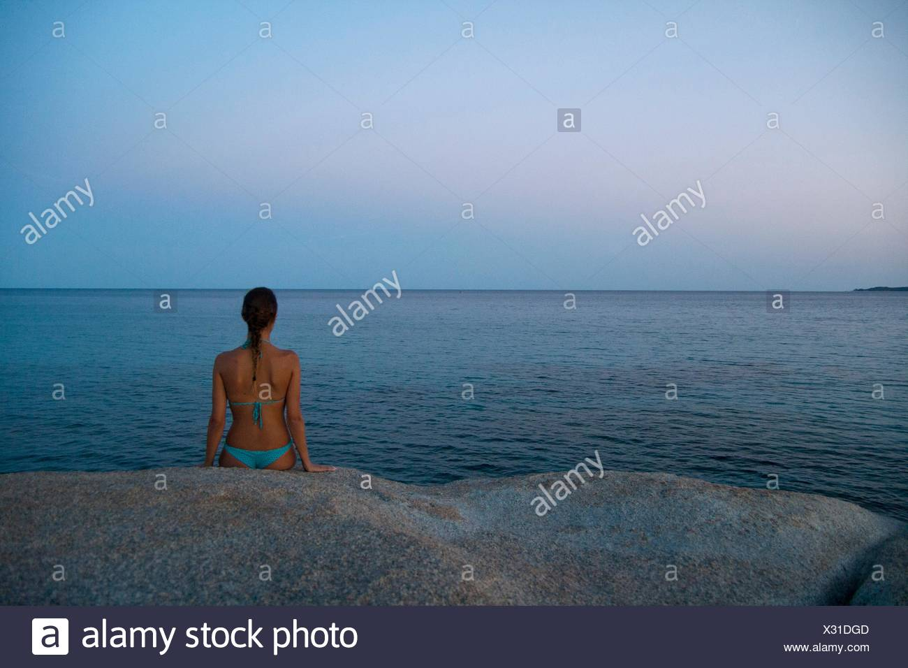 Young woman sitting on rock, looking out to sea, Costa rei, Sardinia, Italy - Stock Image