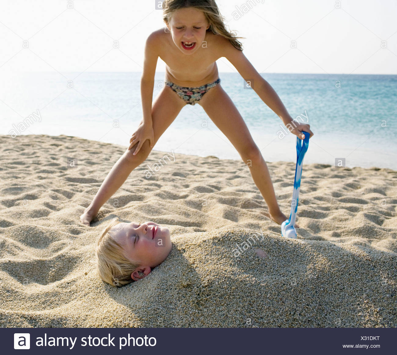 Young girl burying young boy in the sand at the beach . Stock Photo