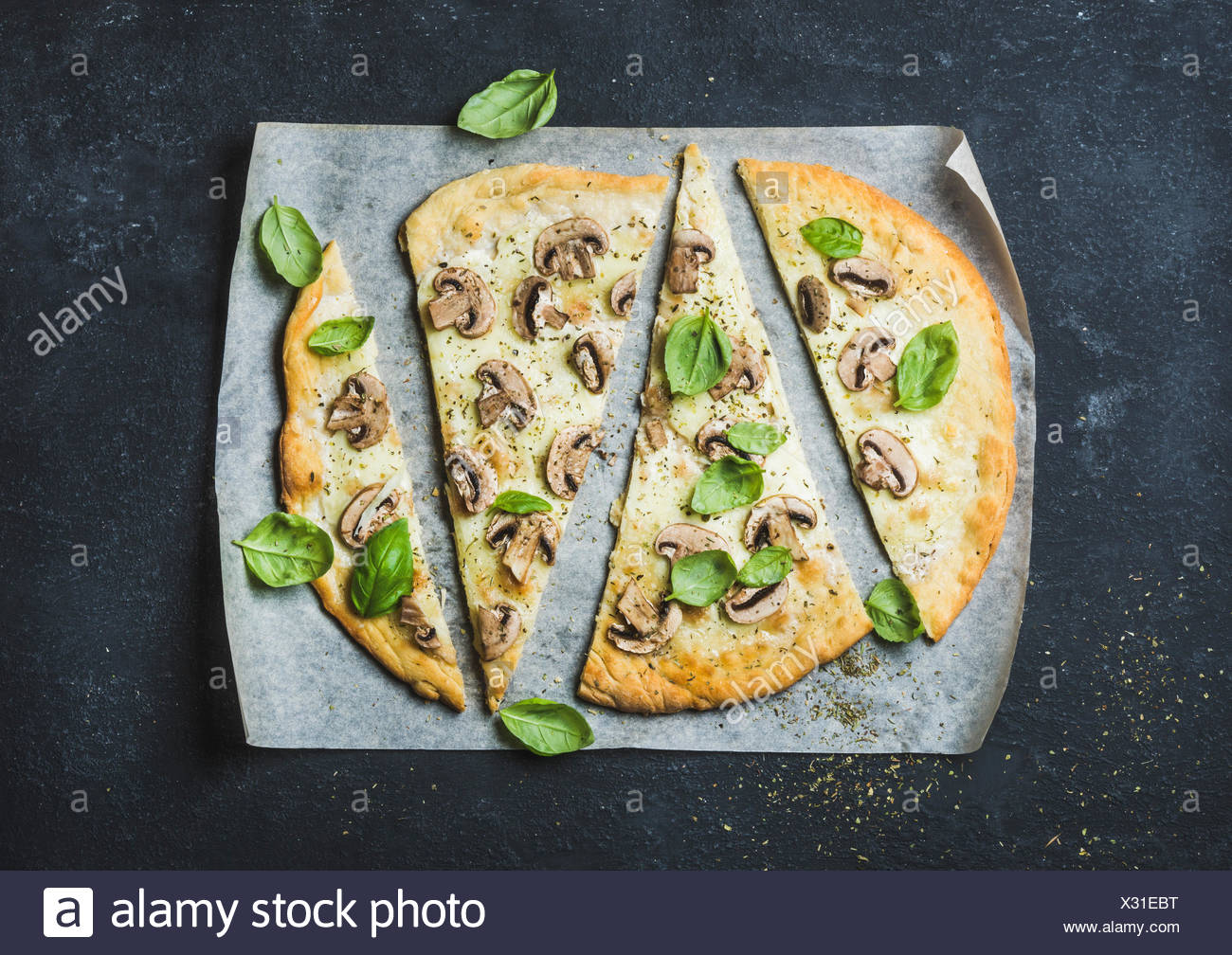 Homemade mushroom pizza with basil cut in slices on baking paper over black stone background, top view, horizontal composition - Stock Image