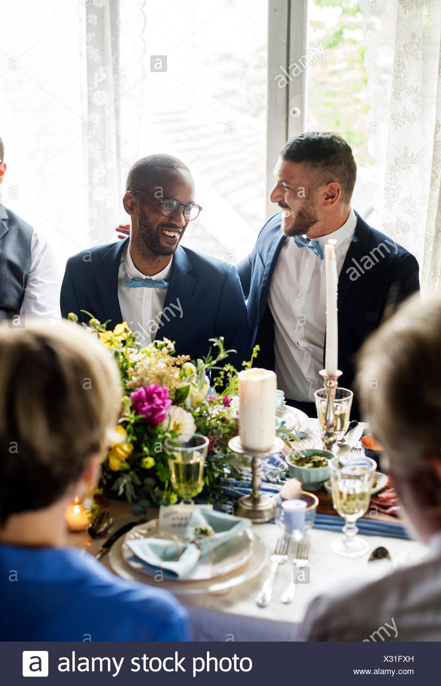 Cheerful Gay Couple in Wedding Reception - Stock Image