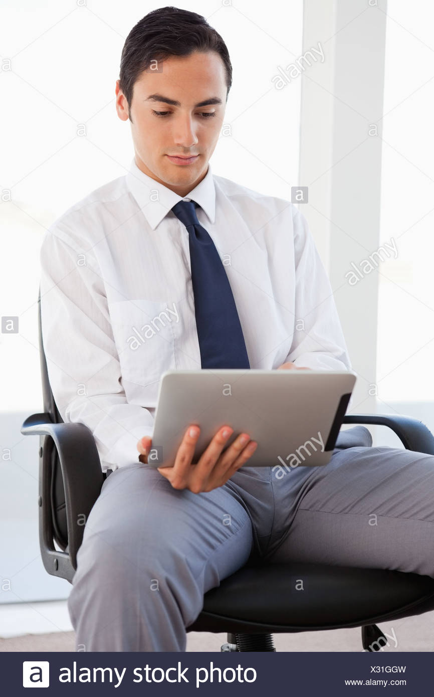 Businessman using a touchpad while sitting - Stock Image