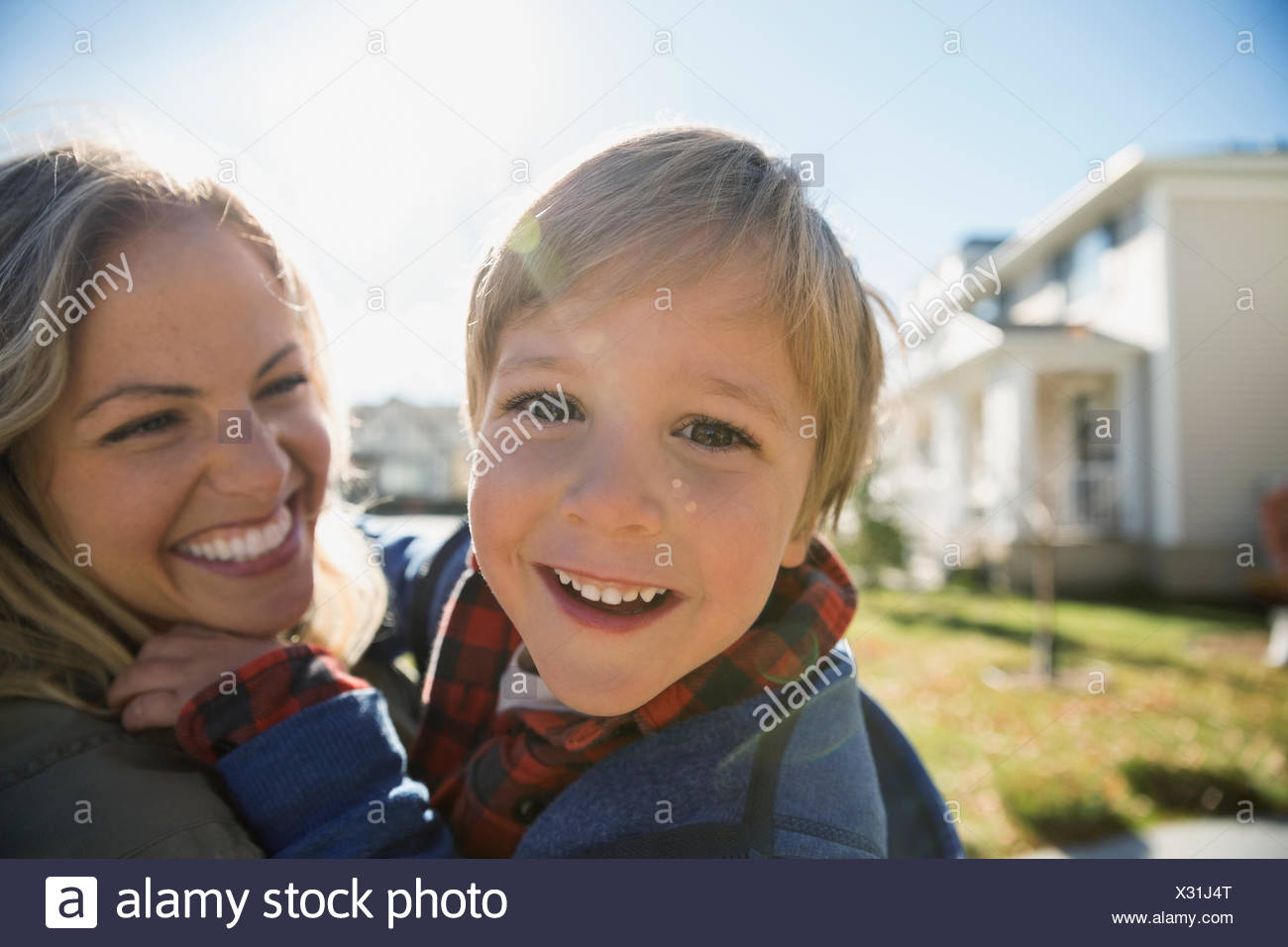 Close up portrait smiling mother holding sun outdoors - Stock Image