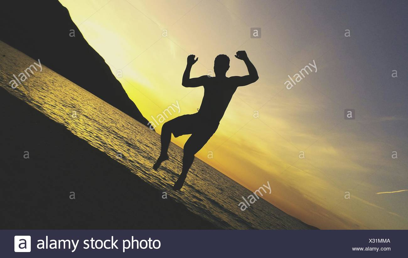 Tilt Image Of Silhouette Man Jumping At Beach Against Sky During Sunset - Stock Image
