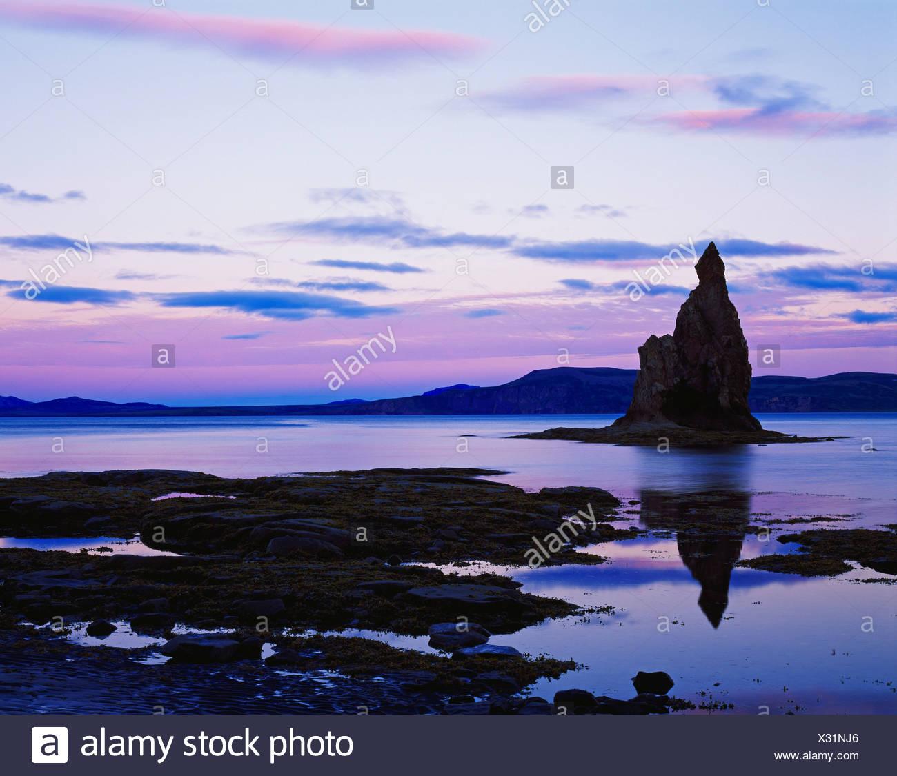 Pastel light sunset silhouetting sea stack tide pools along shore Nunavachak Bay Togiak National Wildlife Refuge Bristol Bay Stock Photo