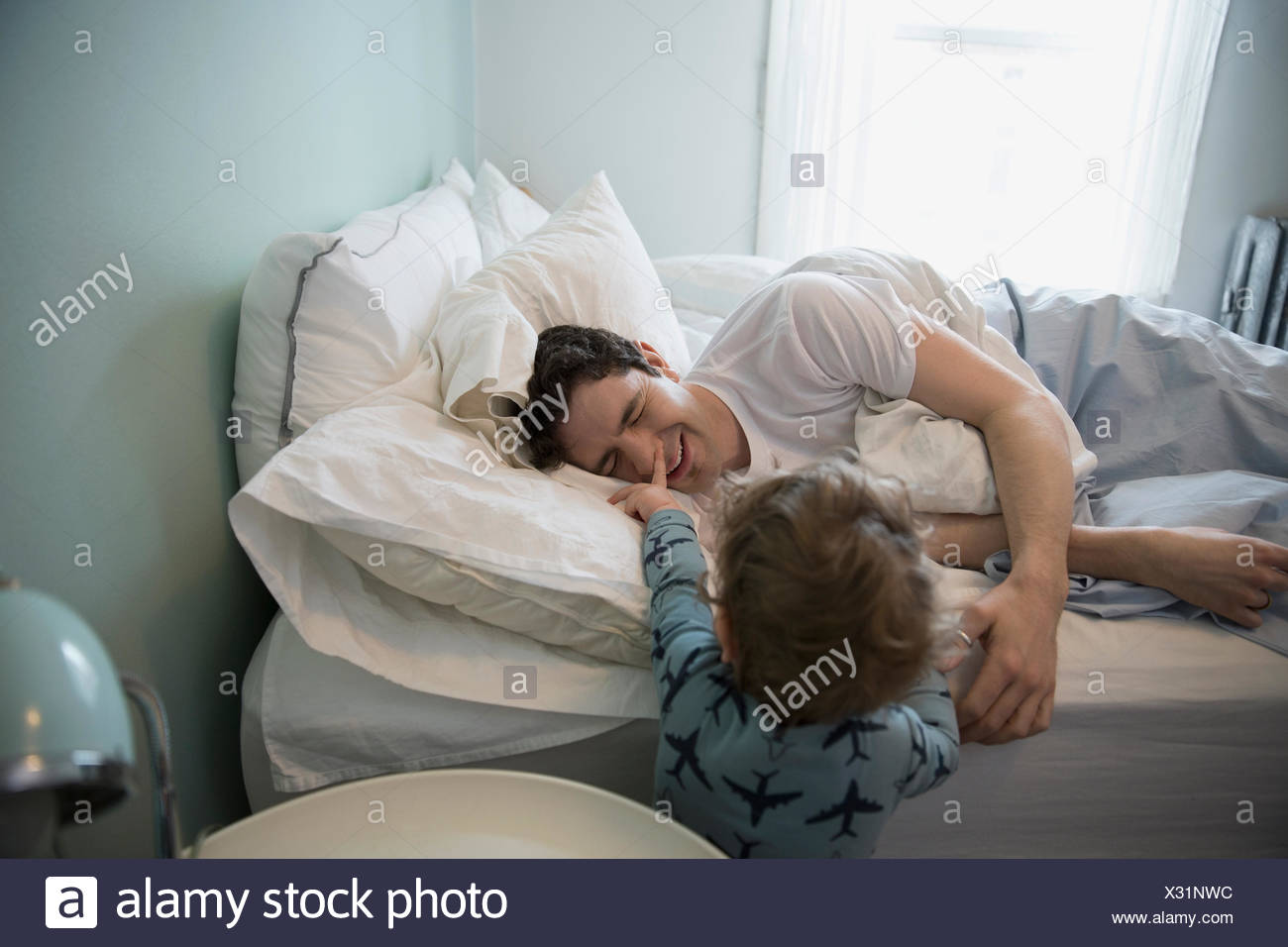 Son waking father by pushing nose - Stock Image