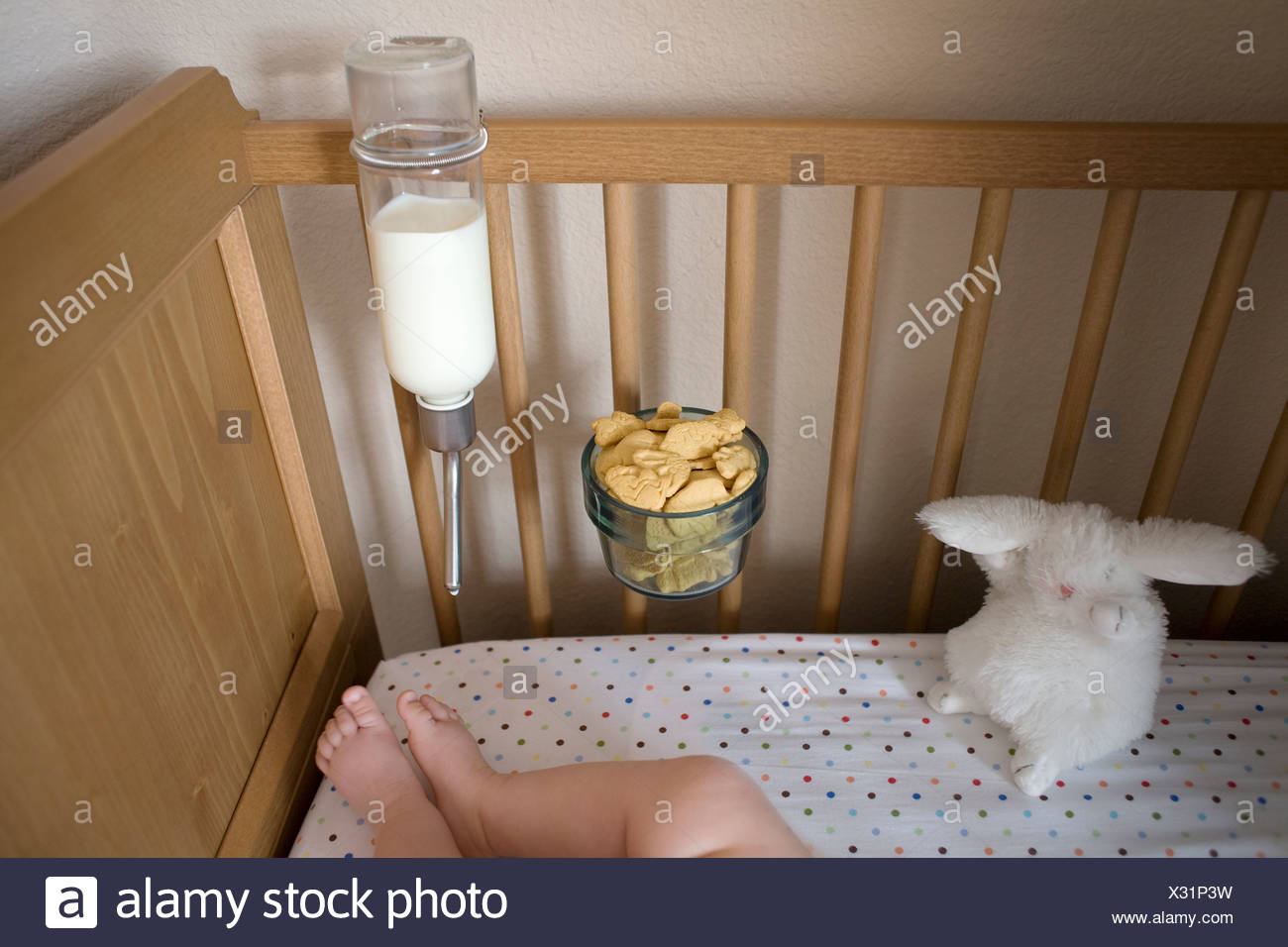 Helpful Ideas for Busy Dads: a feeding machine in cot Stock Photo
