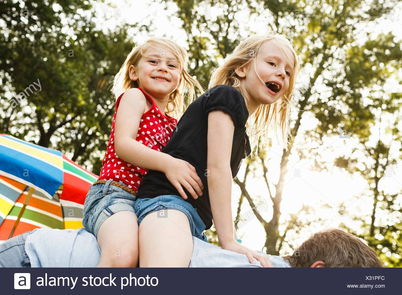 Mature man giving two young daughters piggy back in park - Stock Image