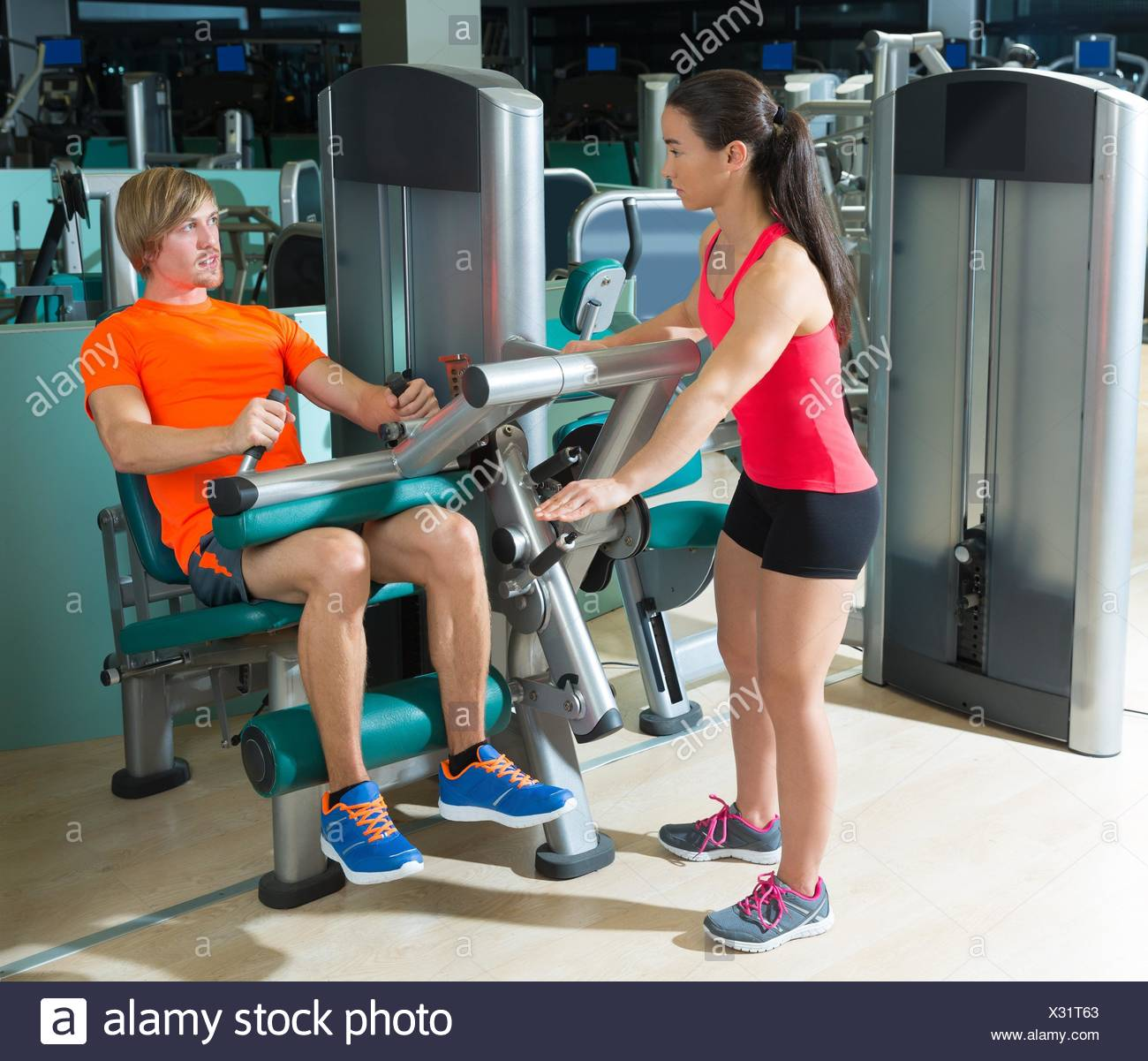 Gym seated leg curl machine exercise blond man and personal trainer