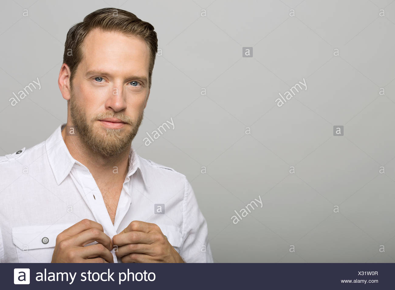 Portrait of confident man buttoning shirt - Stock Image