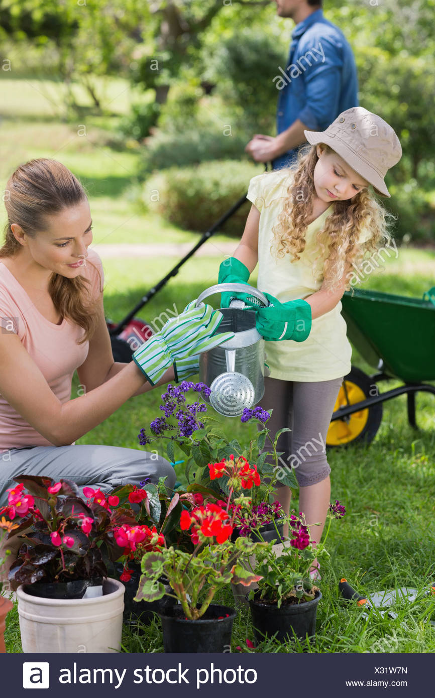 Mother with daughter watering plants - Stock Image