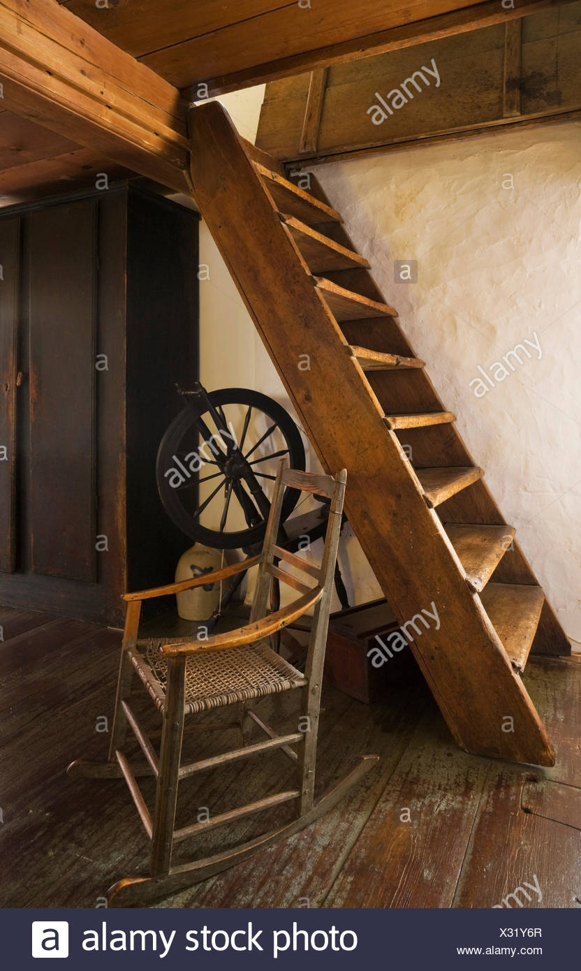 Old wooden rocking chair and spinning wheel next to attic stairs in (1785) fieldstone : wooden attic stairs  - Aeropaca.Org