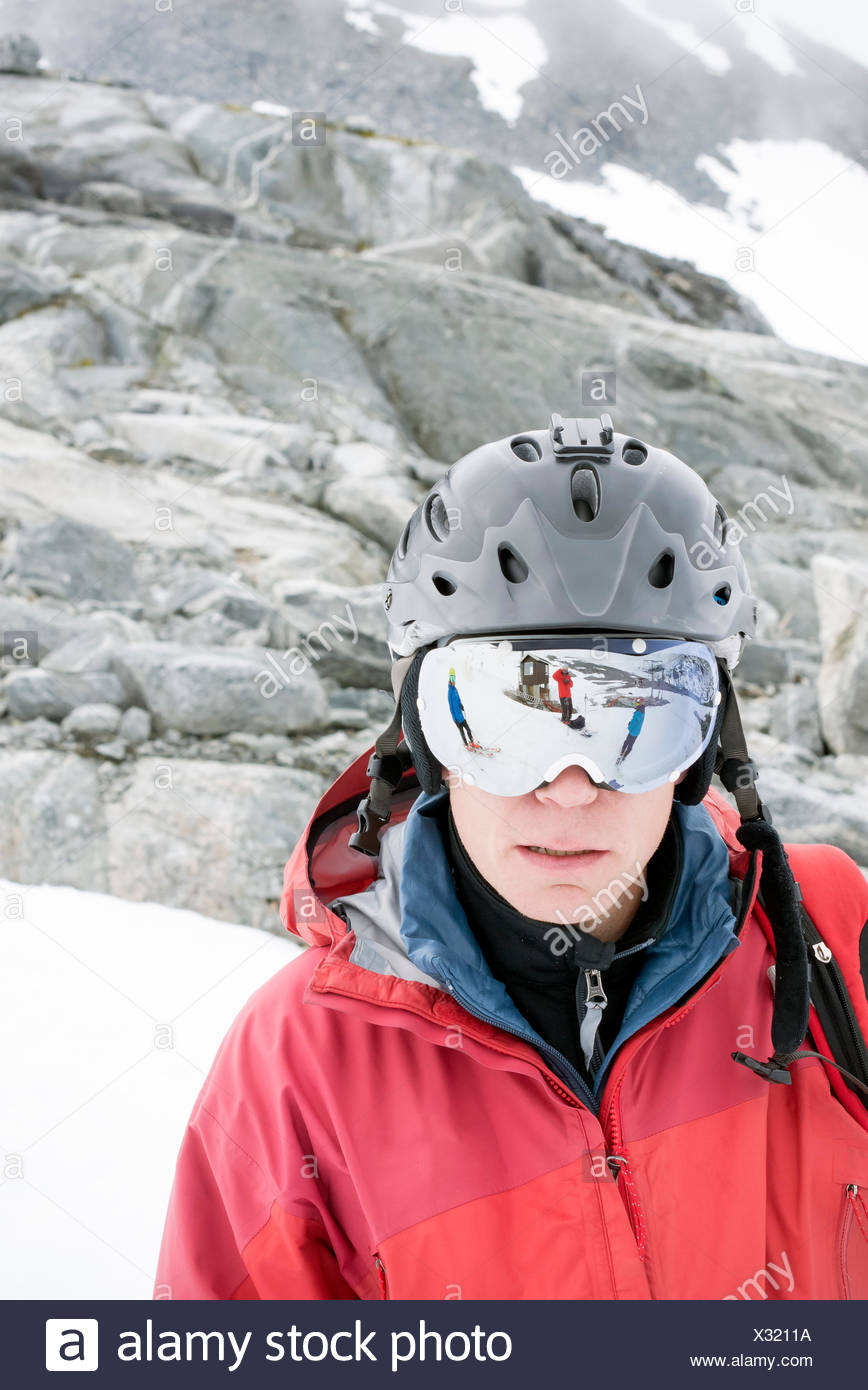 Portrait of man wearing helmet and ski goggles - Stock Image