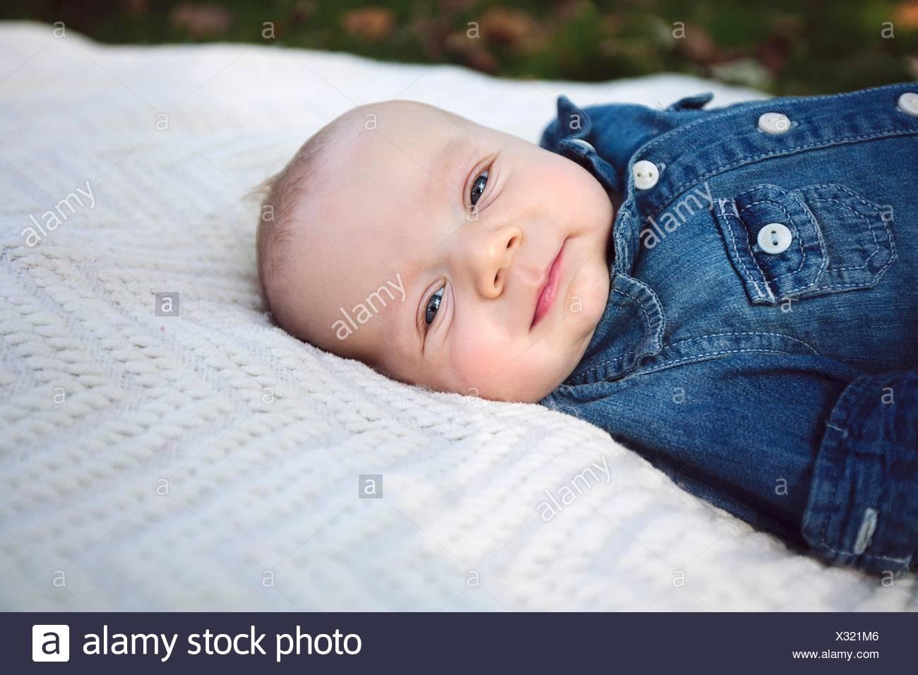 Side view of baby boy wearing denim shirt lying on blanket looking at camera smiling - Stock Image
