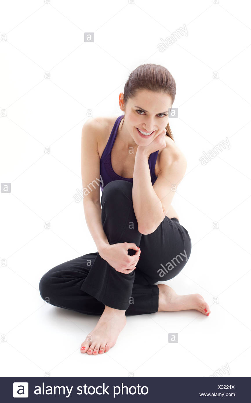 MODEL RELEASED Woman sitting on the floor smiling studio shot. - Stock Image