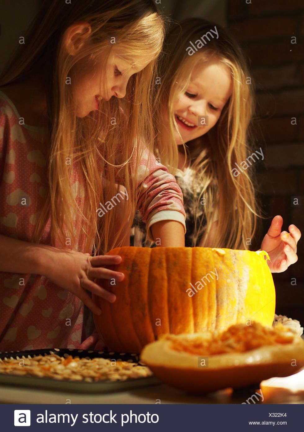 Sweden, Girls preparing (6-7), (8-9) the pumpkin for halloween - Stock Image