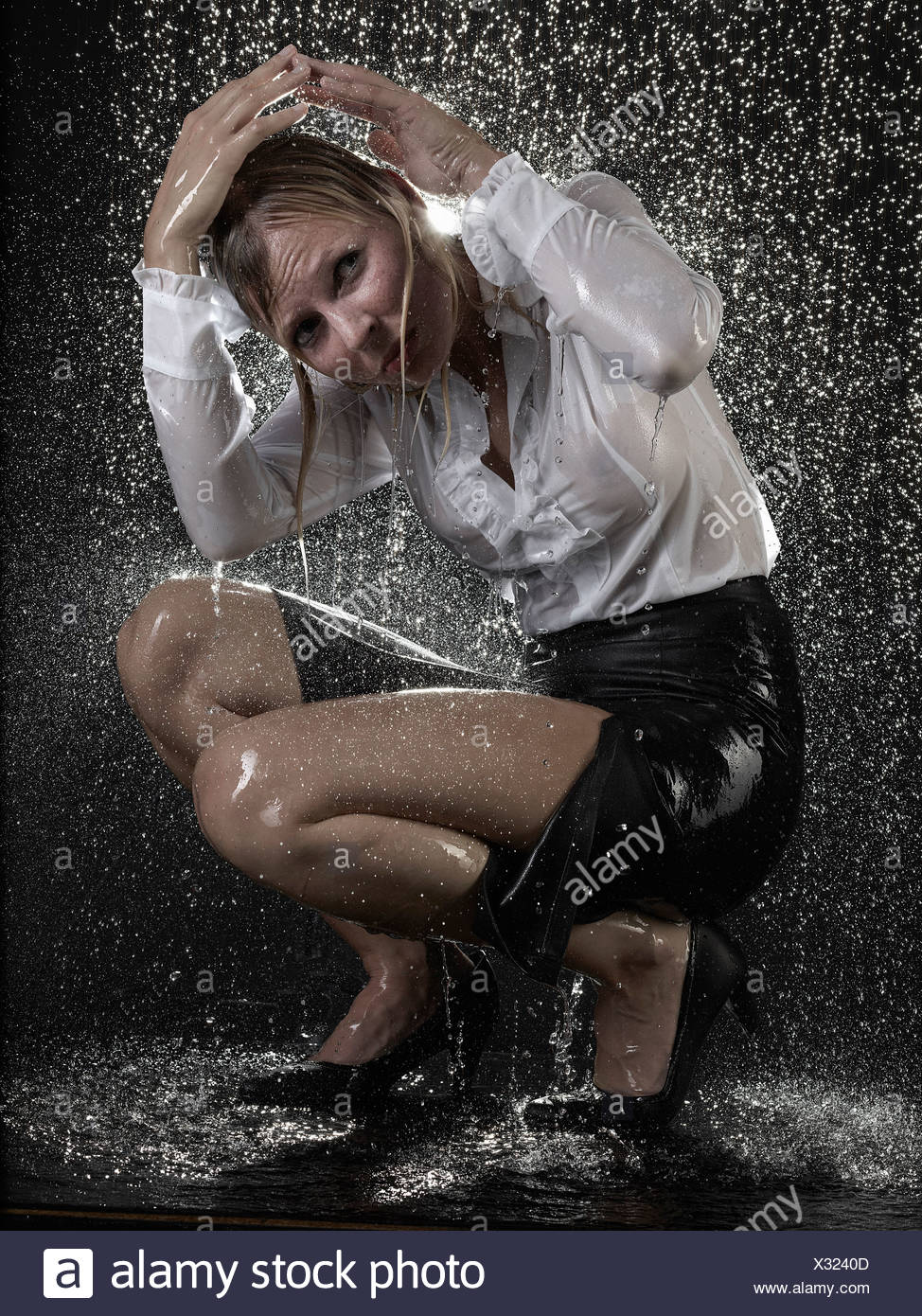 Businesswoman crouching in rain - Stock Image