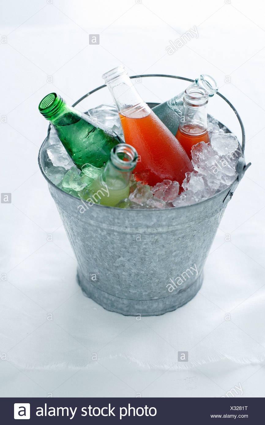 Soda bottles in bucket of ice - Stock Image