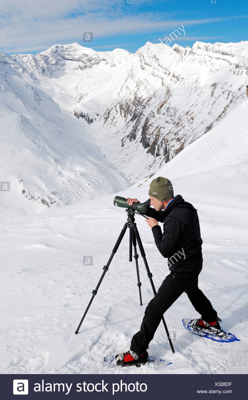 National Park Ranger looking through a spotting scope, Mount Schareck, National Park Hohe Tauern, Carinthia, Austria, Europe - Stock Image