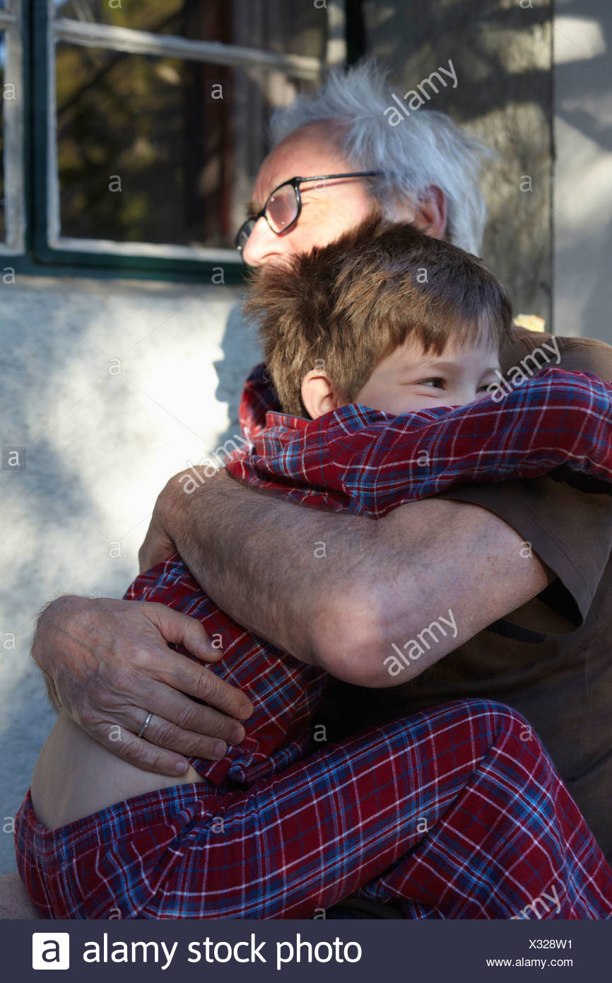 Older man hugging grandson outdoors - Stock Image