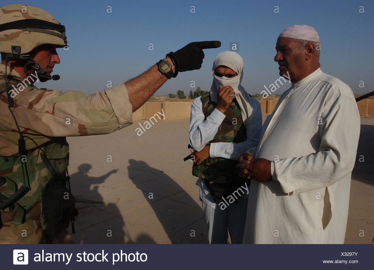 A Staff Sergeant of the 1st Squadron, 2nd Armored Cavalry Regiment talks to an Iraqi in whose home soldiers found two AK-47s, a pistol, and a bag of ammunition. - Stock Image