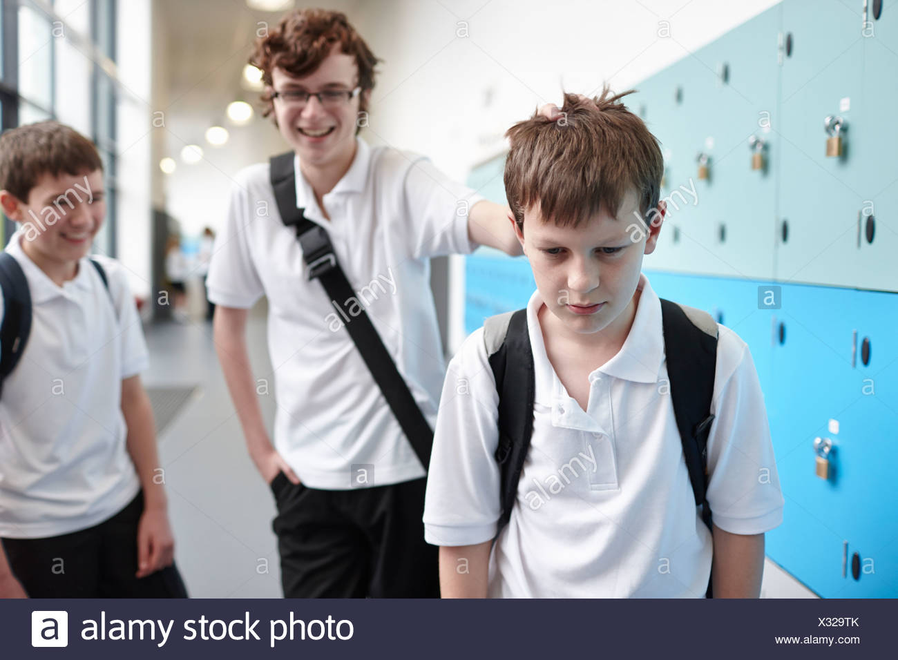 Schoolboy being bullied in school corridor - Stock Image