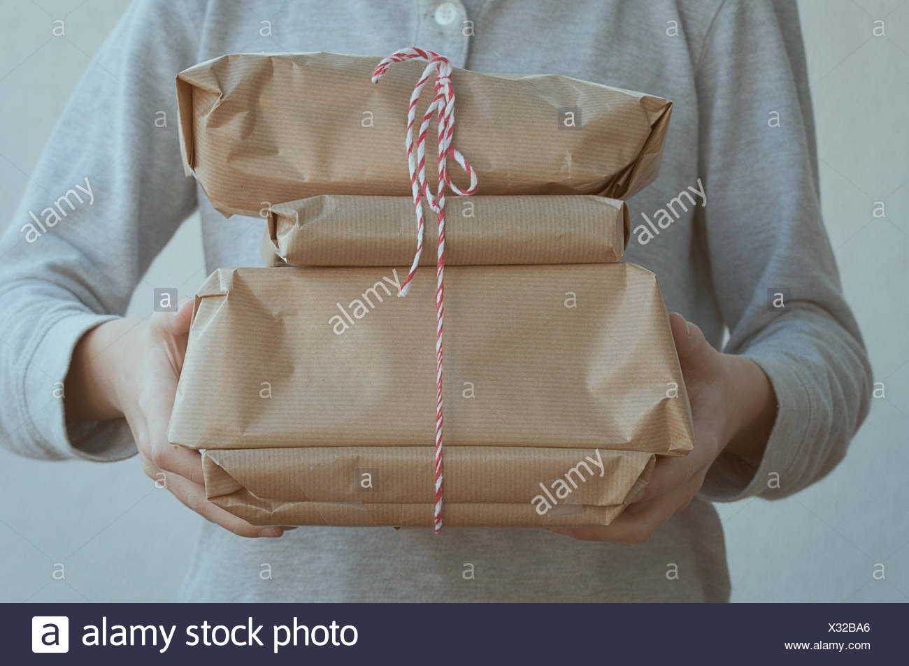 Boy holding a stack of presents - Stock Image
