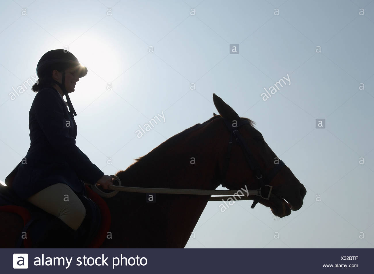 Silhouette of a female jockey riding a horse - Stock Image