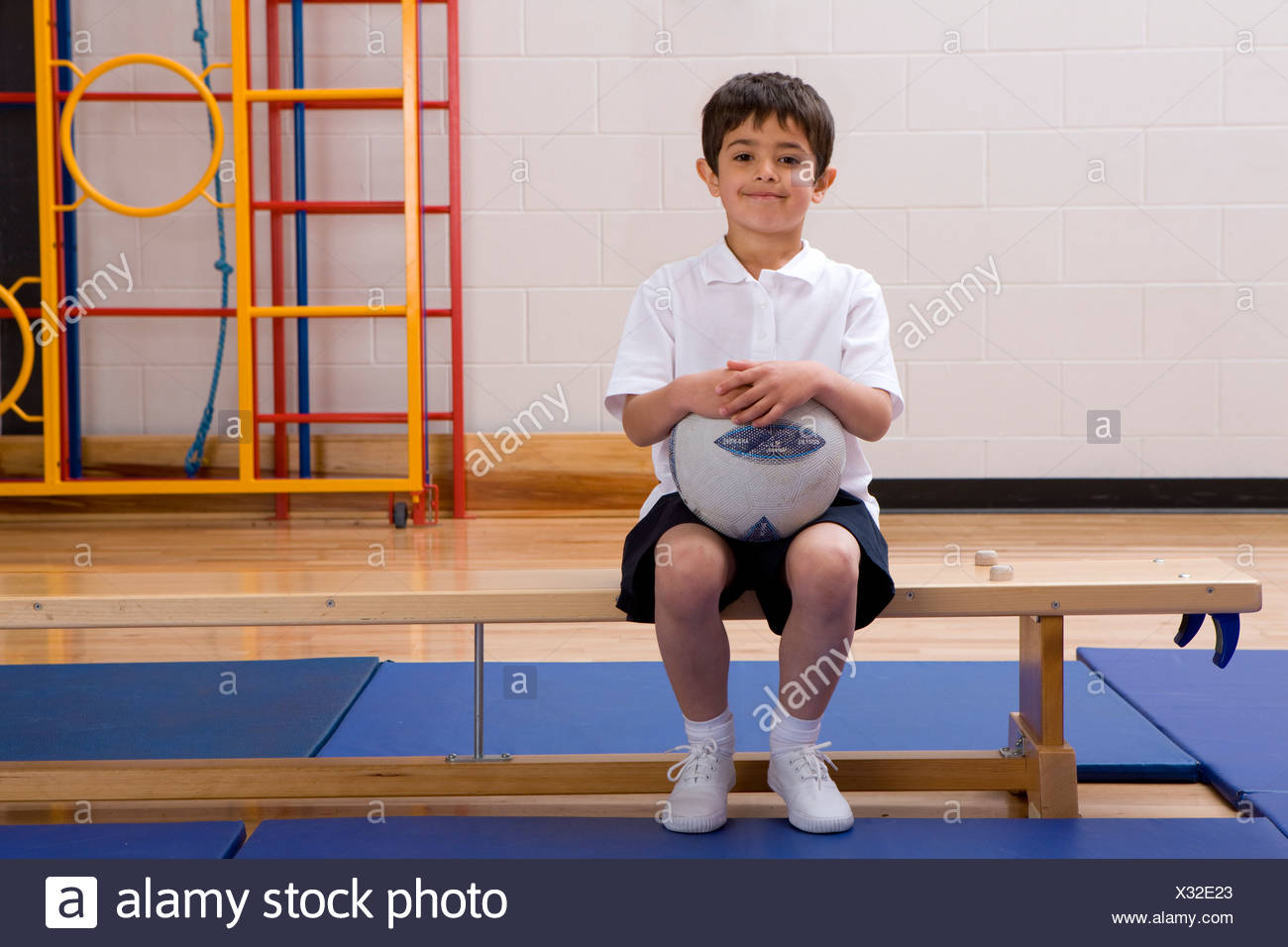 School boy sitting on bench and holding ball in school gymnasium - Stock Image